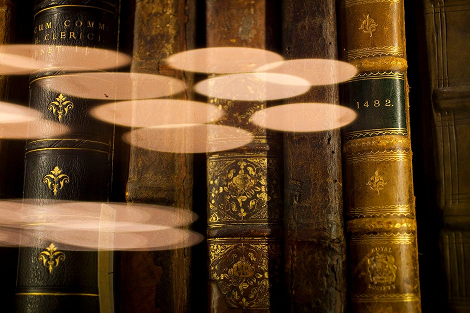 Inside Houghton Library, chandeliers reflect off a glass case housing elegantly bound 15th century volumes. Stephanie Mitchell/Harvard Staff Photographer