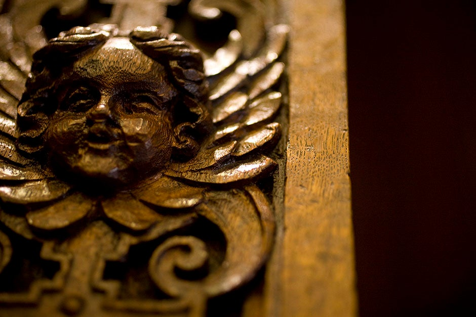 A cherubic figure adorns a grandfather clock in the Thompson Room of the Barker Center. Stephanie Mitchell/Harvard Staff Photographer