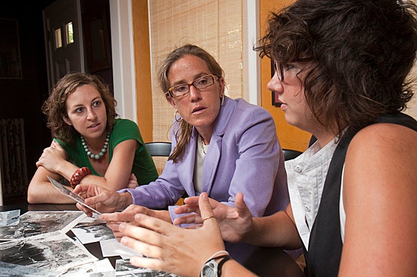 "Professor of history Caroline Elkins (center), doctoral student Erin Mosely (left), and recent graduate Megan Shutzer examine photos collected for an upcoming exhibit that will tell the story of Kenya's break from colonial Britain. ""It's not a '1960s, we all fight for freedom' [story]. It has complexity,"" Elkins said."