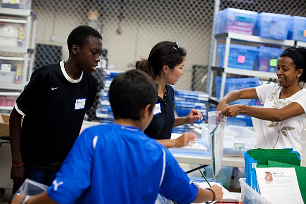 The Harvard Achievement Support Initiative builds on its efforts to engage families by providing homework support kits that will be distributed at the Boston Public Schools' Back-to-School Night sessions beginning in mid-September. Approximately 30 volunteers put together 3,000 kits for students in grades K-5. Helping to accomplish this were Tonnis James (from left), Gabriel Betancourt, Danielle Betancourt, and Maria Monteiro-Roby.