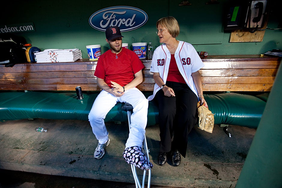 Prior to throwing out the first pitch at Fenway Park for the Red Sox v. Baltimore Orioles game, Harvard President Drew Faust met Red Sox second baseman Dustin Pedroia in the dugout. Rose Lincoln/Harvard Staff Photographer
