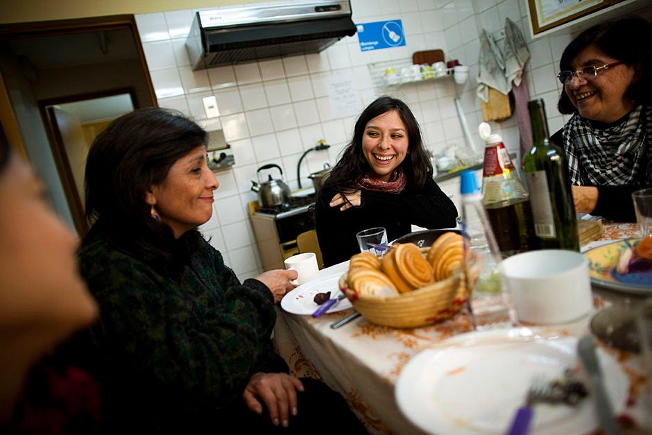 Lunch at the EPES center is a communal gathering and a time to share stories. Calvin (from left), her daughter Isidora Martinez, and Maria Teresa Fuentealba exchange news from the day over a hearty meal accompanied by Chilean breads and wine. Stephanie Mitchell/Harvard Staff Photographer