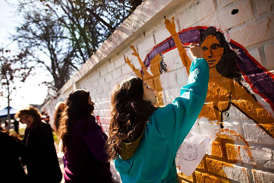 "Martinez (right) and a collection of women from the community paint a mural for the EPES-led anti-violence campaign ""For Me, For You, No + Violence"" in the El Bosque neighborhood. Stephanie Mitchell/Harvard Staff Photographer"