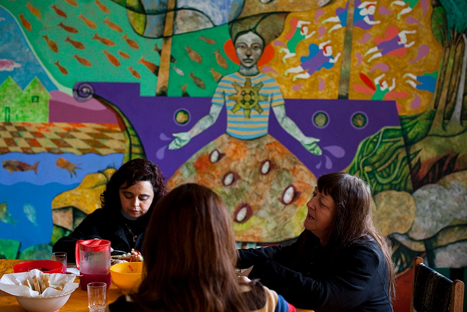 At EPES headquarters in Concepción, the staff, including Maritza Provoste (from left) and Virginia Norambuena, regularly lunches together under this spectacular mural depicting the paths to women's empowerment. Stephanie Mitchell/Harvard Staff Photographer