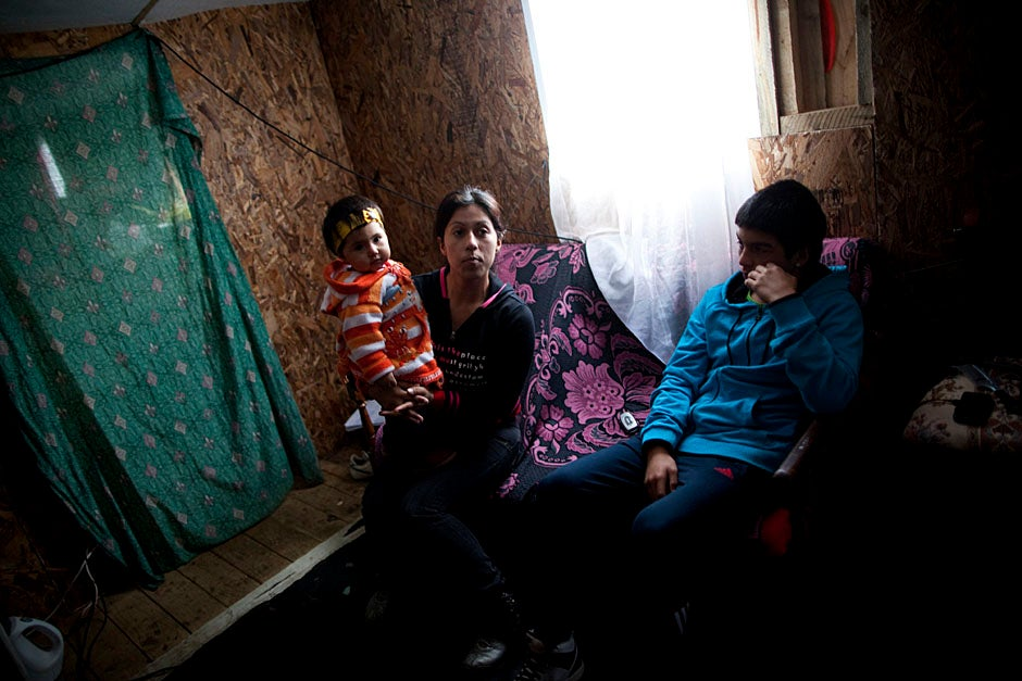 Eleven-month-old Darlene Anis Villegas (from left), Natalia Shendiz, and Luis Archivalas Villegas sit inside their temporary Villa Bosquemar home. Stephanie Mitchell/Harvard Staff Photographer