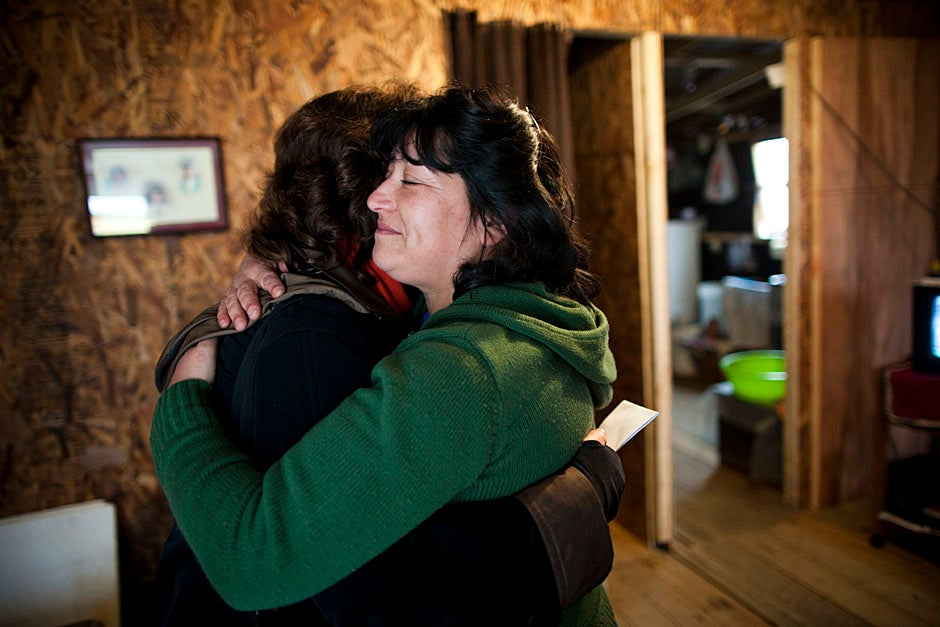 Sandra Rita Mora (right), of Villa Bosquemar, hugs Anderson, who, along with EPES, has helped winterize many temporary homes with material support. Stephanie Mitchell/Harvard Staff Photographer