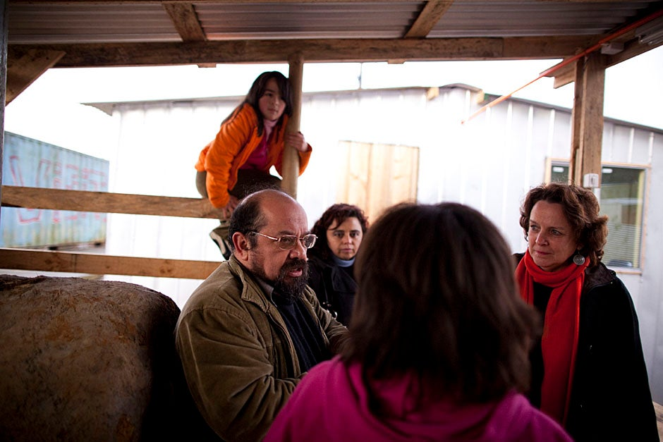 The Villa Bosquemar resettlement camp in Penco is home to 50 families that once lived along the shore and depended on the sea. These independent people, low on schooling and income, are now living in one-room government-issued wooden shelters that lack running water, sharing communal latrines, and using cold-water showers. Constanza Ramirez Villegas (from left), Lopez, Provoste, Nuvia Villegas (Constanza's mother), and Anderson speak in the campamento. Stephanie Mitchell/Harvard Staff Photographer