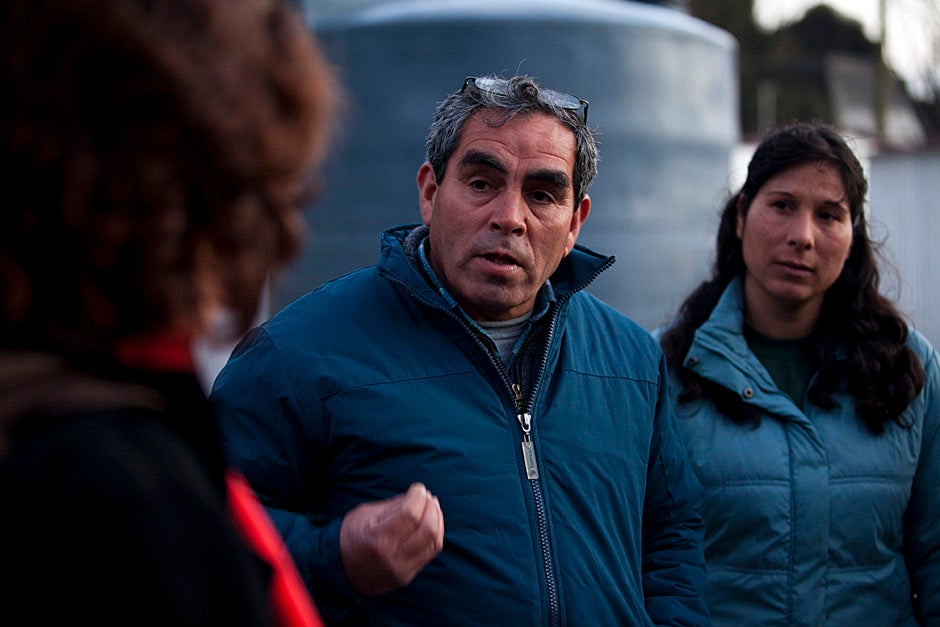 Juan Correa (center), president of Campamento Ebenezer, explains how the roofs of the wooden emergency homes are a new version of the traditional fanolas made with cardboard sheets soaked in tar to make them water-resistant. Unfortunately, water seeps through the roofs and the wind has also carried them away. Correa explains how not only are neighbors having their few belongings ruined or destroyed because of the rain, but many have contracted severe respiratory illnesses. Stephanie Mitchell/Harvard Staff Photographer