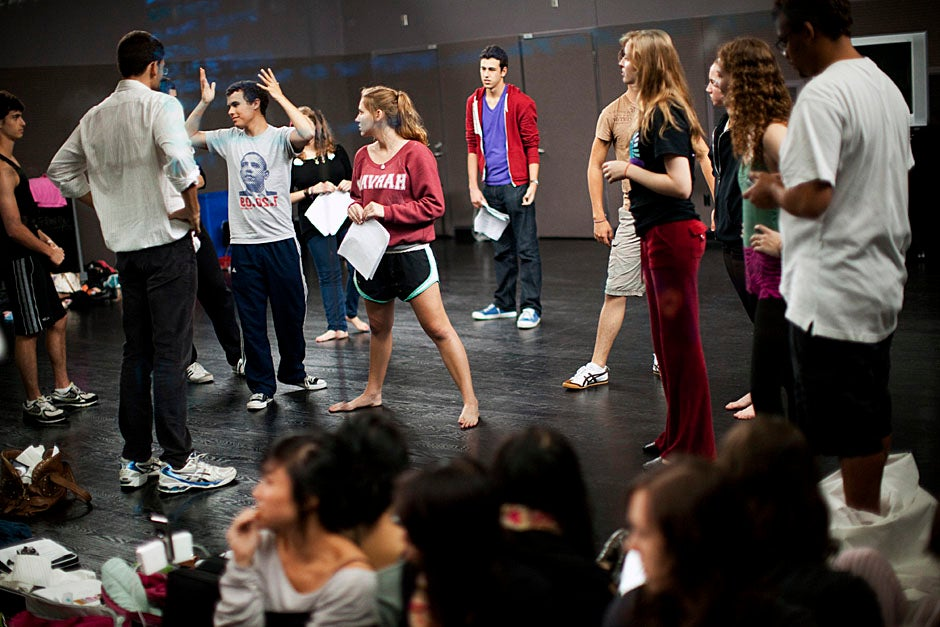 Ben Silva '14 (arms in air) runs lines with his fellow cast members. Stephanie Mitchell/Harvard Staff Photographer