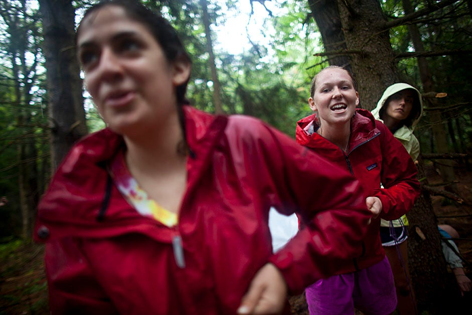 Trip leader Emma Franklin '12 (center) yells encouragement while setting up camp with the help of Leah Schulson (left) and Katya Johns.  Justin Ide/Harvard Staff Photographer