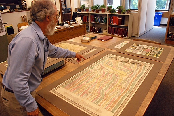 """Research librarian Joseph Garver examines an early 18th century chart depicting various empires in a """"river of time."""""""