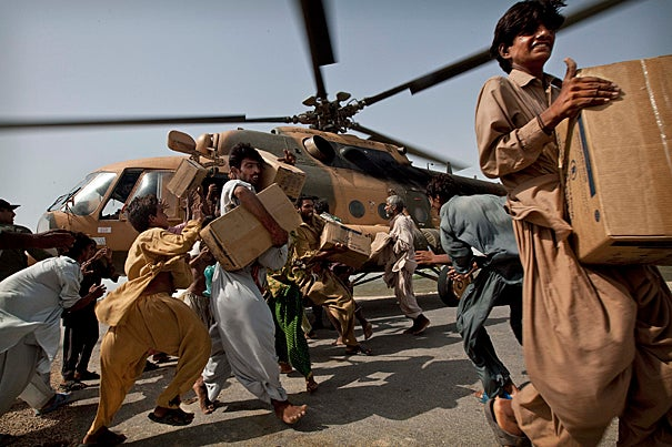 Pakistanis carry boxes of food from an Afghan army helicopter after it landed on a road to deliver emergency food aid in a flooded area of Baluchistan Province, southern Pakistan. According to Harvard water engineer John Briscoe, Pakistan's long-term water security requires institutional renewal and new infrastructure, including new dams, on the Indus River.