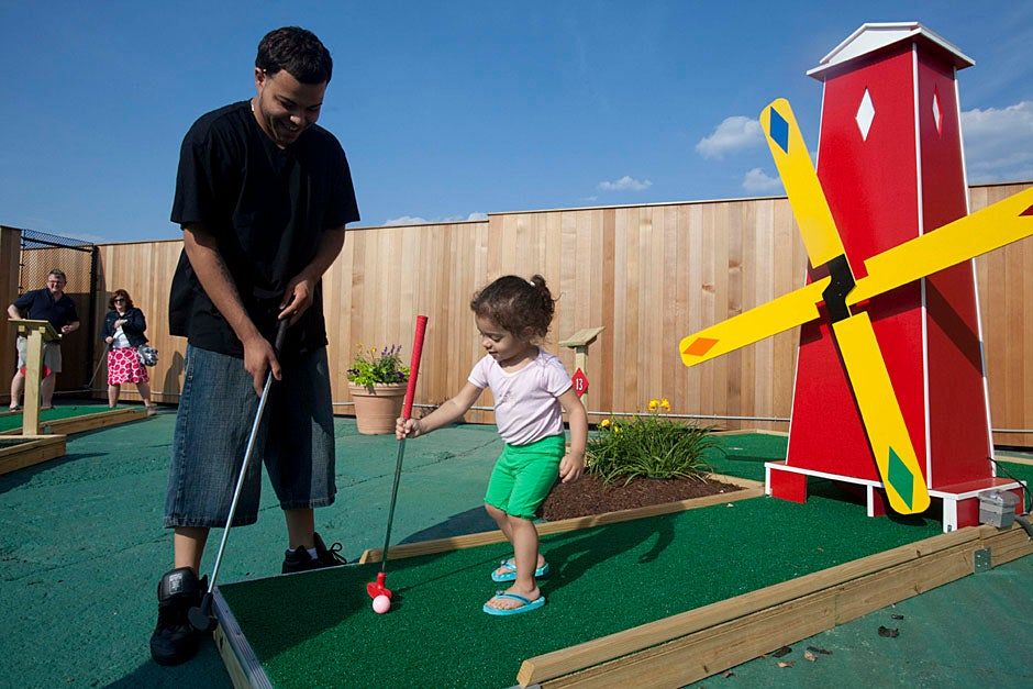 Allston residents play miniature golf during the opening of the Harvard Allston Field and Fairway. Kris Snibbe/Harvard Staff Photographer