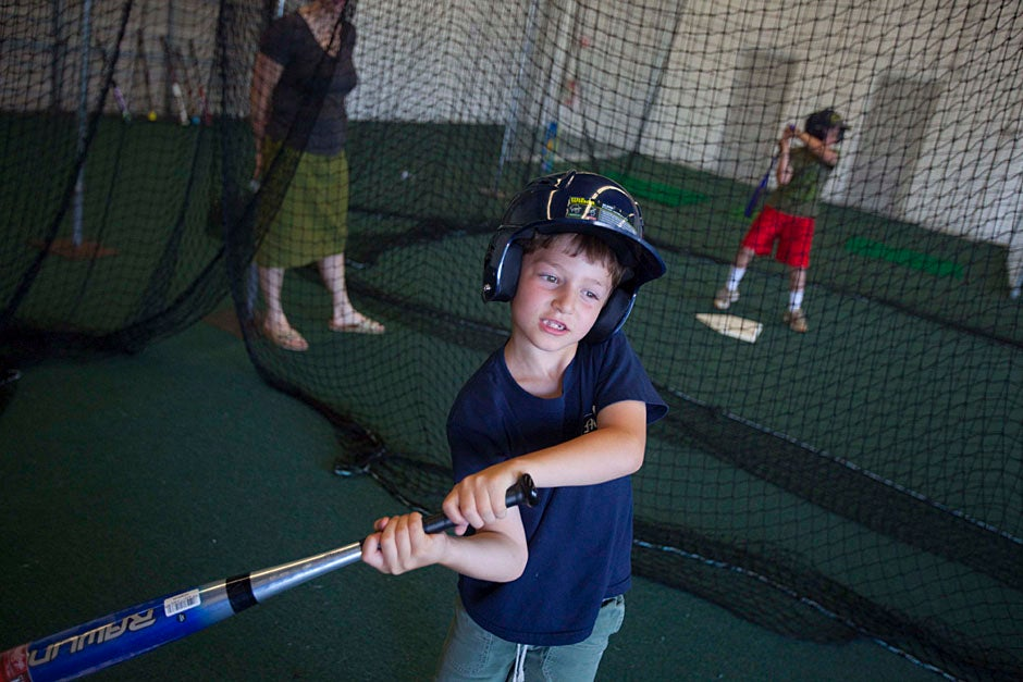 A Brighton family enjoys the batting cages at the Harvard Allston Field and Fairway.  Kris Snibbe/Harvard Staff Photographer