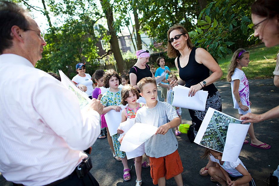 Harvard designers Dennis Swinford (left) and Emily Mueller De Celis (with sunglasses) lead children on a tour of the Library Park site.  Stephanie Mitchell/Harvard Staff Photographer