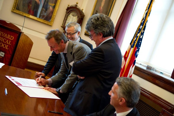 Ernesto Bertarelli (center) signs an agreement providing $9M from the Bertarelli Foundation to establish a joint research and education program between Harvard Medical School and Ecole Polytechnique Fédérale de Lausanne in Switzerlandand. William Chin (from left), Patrick Aebischer, and Didier Burkhalter look on. Chin will hold the first Bertarelli Professorship in Translational Medical Science and oversee the development of the new joint program.