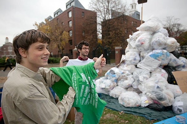 Brandon Geller '08 (left) and Sam Arnold '14 stand beside Mount Trashmore in front of the Science Center. One day every fall, students and staff construct the pile, which represents one day's trash from Harvard Yard.
