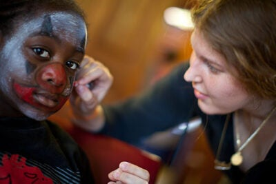 Seven-year-old DJ Pate of Boston has his face painted by PBHA's Kathryn Wilcox '11.