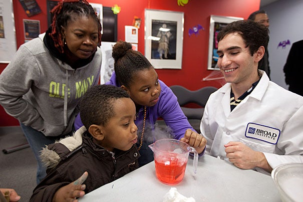 Allston resident Lude Telfort and her children, Jordan Francis, 3, and Prya Francis, 11, learn about dry ice and chemistry from Brandon Silverman '12 inside the Harvard Allston Education Portal during the Halloween-themed community event.