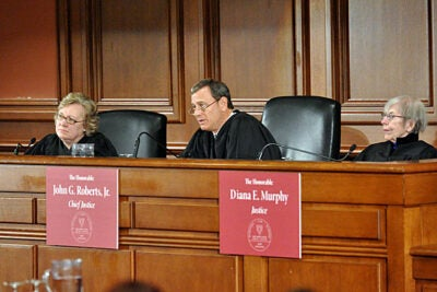 Julia Smith Gibbons (from left) of the United States Court of Appeals for the Sixth Circuit, U.S. Supreme Court Chief Justice John G. Roberts Jr. '76, J.D. '79, and Diana E. Murphy of the United States Court of Appeals for the Eighth Circuit preside over the final of the rigorous Ames Moot Court Competition at Harvard Law School.