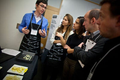 "Cody Evans (left) and Sophie Wharton (center) explain to chefs from the Alicia Foundation in Spain about their project, ""Parmesan Noodles.""  The trick was making pasta out of cheese."