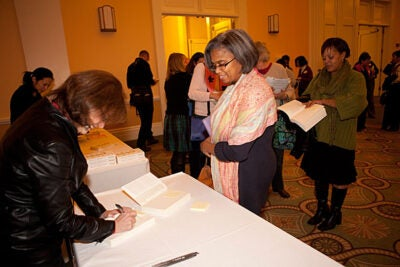 Ellen Galinsky (left) signs her book for Cynthia Jacobs-Tolbert, assistant principal of John Marshall Elementary School in Dorchester.