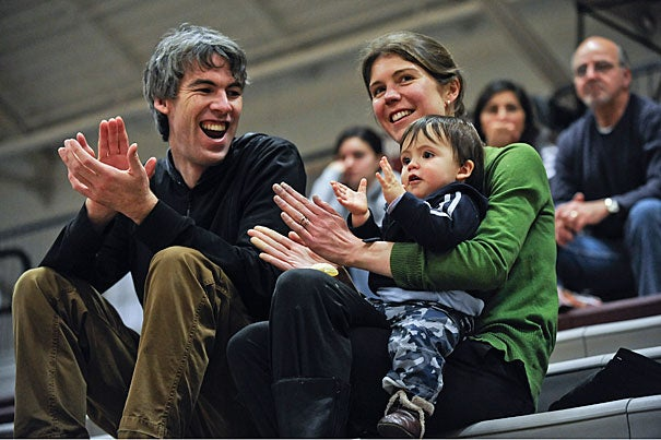 Cambridge residents Nick Petrie and his wife, Sarah, get a kick out of 11-month-old Oliver applauding a nice play by the Crimson. The Harvard-UMass game capped a series of three Community Days sponsored by the Harvard men's and women's basketball teams that offered free admission to Cambridge and Allston-Brighton residents over the winter break.