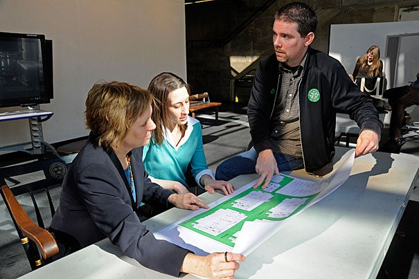 Graduate School of Design staffers Kate Eaton (center) and Trevor O'Brien look over plans showing Gund Hall green initiatives with Laura Snowdon (left), dean of students.