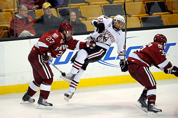 Crimson forward Michael Biega '11 (left) sends a Northeastern player flying with a hard check as Conor Morrison '13 (right) skates past. Northeastern walked away with a 4-0 win in the opening round of the annual Beanpot tournament.