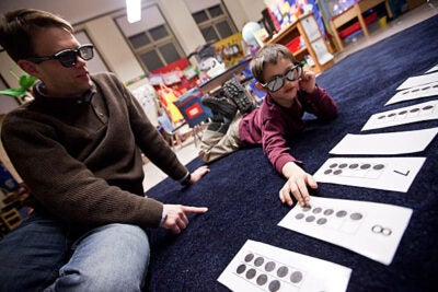 "Sean Andersson (left) works on a math problem called ""X-ray vision"" with his son Ethan, 5, at the Gardner Pilot Academy. Math Night was the latest of Harvard's many collaborative efforts with the school."