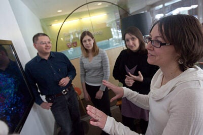 Professor Paola Arlotta (far right) discusses an image of neurons with graduate student Simona Lodato (right to left), Professor of Neurology Kathleen Quest, and Professor of Molecular and Cellular Biology Tako Hensch. The study's findings could potentially help future researchers to better understand the circumstances that lead to errors in the building and functioning of brain circuitry.