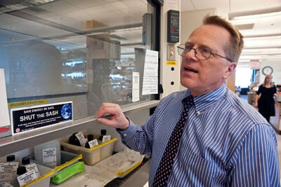 """Allen Hebert, HMSenergy specialist, demonstrates the """"Shut the Sash"""" in a lab at the New Research Building."""