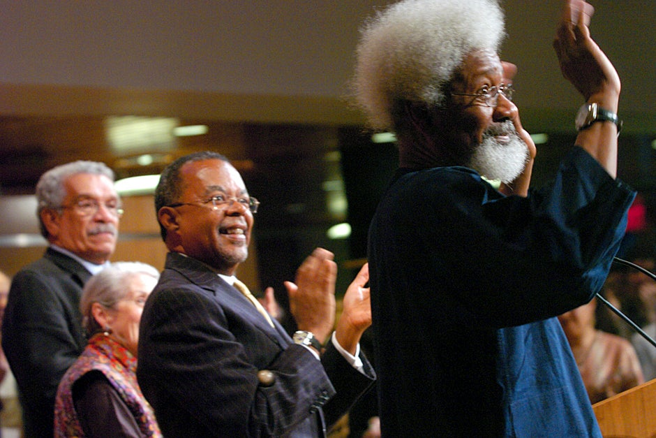 "April 27, 2005. ""A Season of Laureates: Readings in Honor of the 70th Birthday of Wole Soyinka"" pays homage to literary giant and human rights activist Wole Soyinka (right), who receives a standing ovation from the crowd. Derek Walcott (from left), Nadine Gordimer, and Henry Louis Gates Jr. applaud. Photo by Stephanie Mitchell/Harvard Staff Photographer"