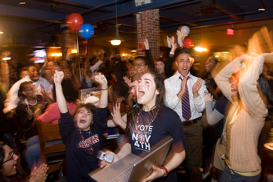 Nov. 4, 2008. Sara Stern '12 (holding laptop) joins students from the Harvard Black Students Association and the Black Pre-Law Association inside the Queen's Head Pub to watch the election results from the presidential race between John McCain and Barack Obama. Photo by Kris Snibbe/Harvard Staff Photographer
