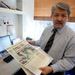 """Historian Baktybek """"Bakyt"""" Beshimov, a 2010-2011 fellow in Harvard's Scholars at Risk program, holds a newspaper from his native Kyrgyzstan in his office at the Davis Center for Russian and Eurasian Studies. It featured him dressed as the Statue of Liberty — a """"spy for the West"""" — at a time when his opposition political views put his life at risk."""