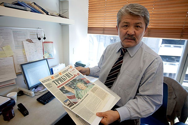 "Historian Baktybek ""Bakyt"" Beshimov, a 2010-2011 fellow in Harvard's Scholars at Risk program, holds a newspaper from his native Kyrgyzstan in his office at the Davis Center for Russian and Eurasian Studies. It featured him dressed as the Statue of Liberty — a ""spy for the West"" — at a time when his opposition political views put his life at risk."