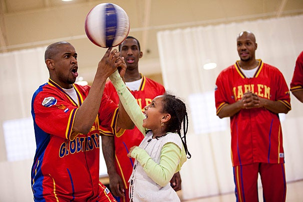 A Harlem Globetrotter, who calls himself Scooter (left), asked Betunia Zelenlem to come down from the bleachers so he could teach her how to do the classic Globetrotter spin.