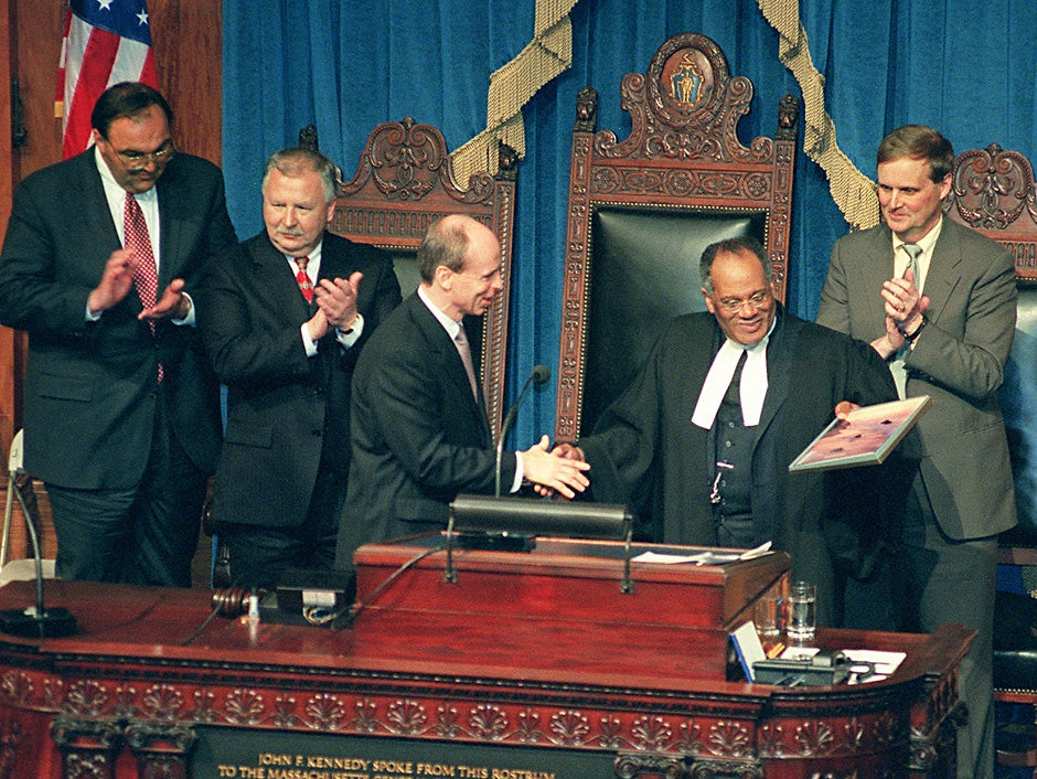 """Rev. Peter J. Gomes addresses the Massachusetts House of Representatives in 2000 as part of Speaker of the House Thomas M. Finneran's Lyceum series, which brings special guests before the House to present their thoughts on a wide range of topics. After speaking eloquently and humorously about """"The Common-Wealth and the Civic Imagination: Cherishing the Public Mind,"""" Gomes receives a book from Finneran. Rose Lincoln/Harvard Staff Photographer"""