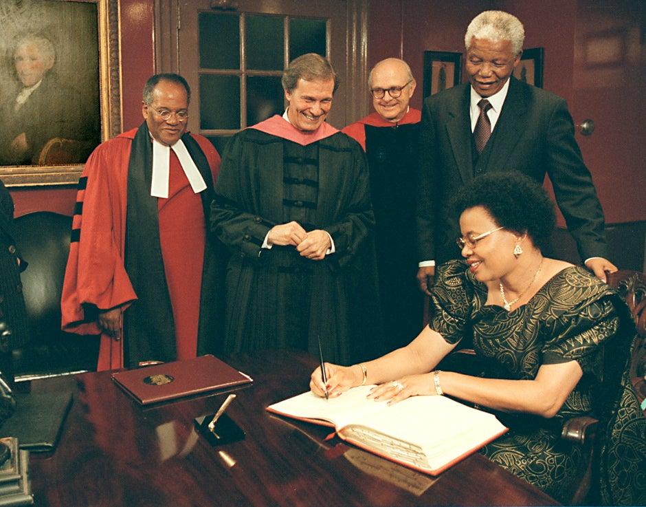 The Rev. Peter J. Gomes (from left), Harvard President Neil Rudenstine, University Marshal Richard Hunt, and Nelson Mandela watch as Mandela's wife, Graça Machel, the former First Lady of Mozambique, signs Harvard's guestbook. Mandela and Machel visited Harvard on Sept. 18, 1998 for a special convocation honoring Nelson with an honorary degree. Mike Quan/Harvard Staff Photographer