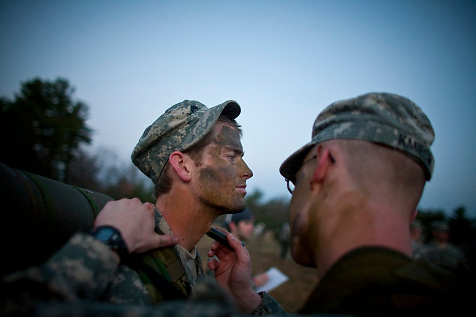 """David Boswell '10 (left) has camo paint applied by a squad member as they ready for training early in the monring. Members of the Paul Revere Battalion Army ROTC program, including students from Harvard University, participated in the annual spring week end training exercise at Fort Devens in April 2008. Called """"FTX,"""" it is training exercise for students held twice a year.  Justin Ide/Harvard Staff Photographer"""