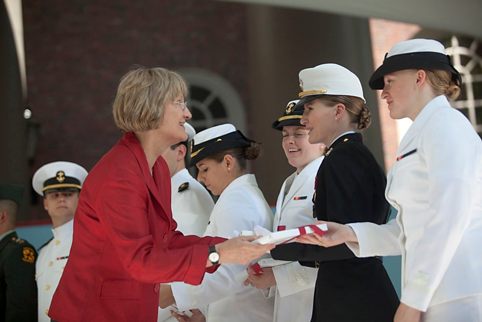 During the 2010 ROTC commissioning ceremony, Harvard President Drew Faust gives a gift to Shawna Sinnott '10 (black jacket) and Olivia Volkoff '10 (white jacket). Kris Snibbe/Harvard Staff Photographer
