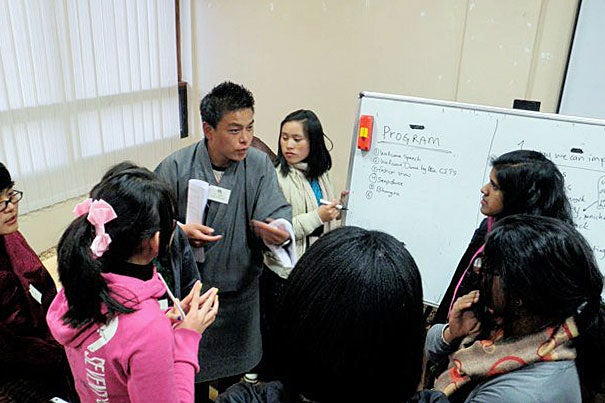 A trainer takes lead in a discussion with Harvard volunteers working with Bhutanese youth.