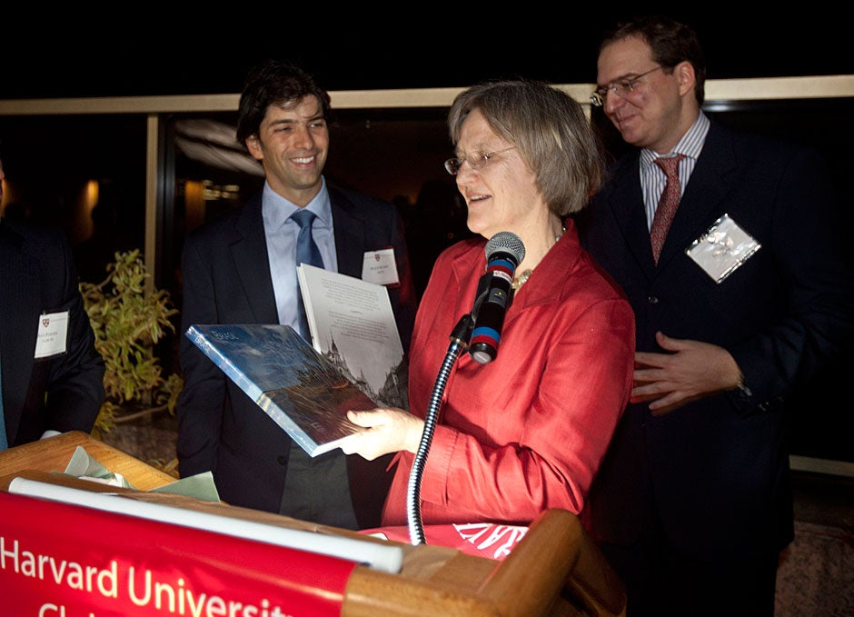 March 24, 2011. Wolff Klabin '96 (left) and Samuel Elia '04 present Harvard President Drew Faust with a book about Brazil during a gathering of Harvard alumni in Rio de Janeiro. Photo by Kris Snibbe/Harvard Staff Photographer