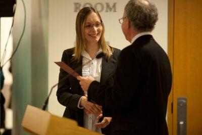 Dean of the Graduate School of Arts and Sciences Allan Brandt presents Viktoriia Liublinska with the Derek C. Bok Award. Liublinska was one of five recipients of the award.