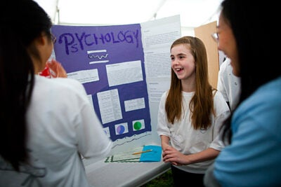 Cambridge students showcased their science and engineering projects as part of a citywide science festival. In a tent near Harvard's Pierce Hall, student Lillian Blanchard (center) discussed her research.