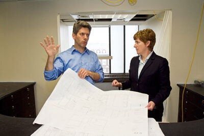 Architect Ted Galante looks at blueprints with Vice President for Campus Services Lisa Hogarty at the Campus Service Center on the 8th floor of Holyoke Center, which is currently under construction, and will combine the Parking Office, ID Services, and Harvard University Housing all in one location.