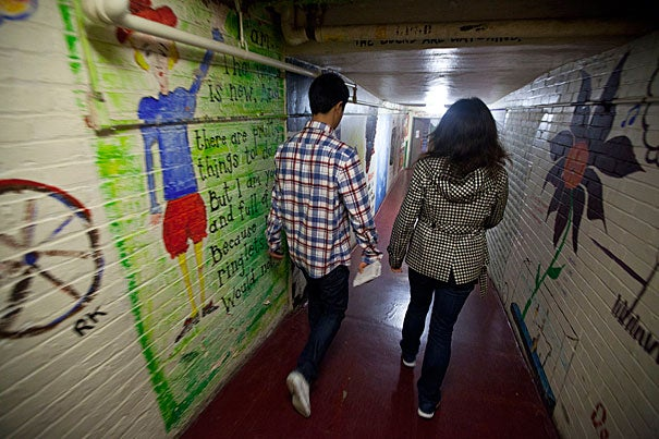 Passersby walk through the colorful Adams House tunnels.