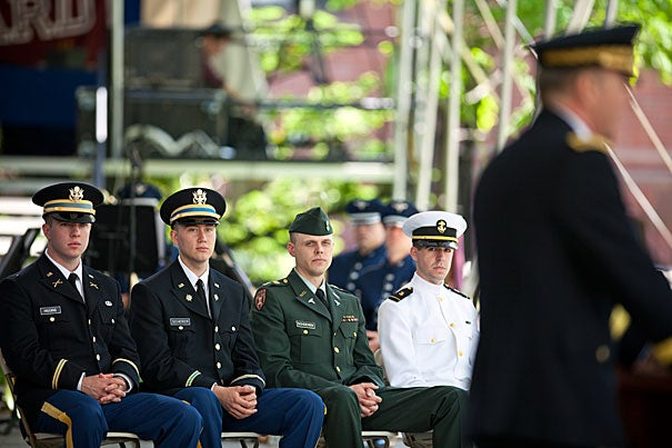 Maj. Gen. James C. McConville (at podium) was the keynote speaker at the ROTC commissioning ceremony. Christopher Higgins (from left) and Aaron R. Scherer, both 2nd lieutenants in the Army, and Navy Midshipman James D. Reach (far right) were commissioned. Cadet Michael Schoenen will take his oath as an officer when he completes his A.L.M. thesis at the Harvard Extension School.
