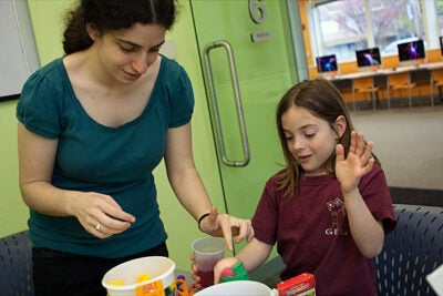 Ed Portal mentor Abby Schiff '11 teaches Allston-Brighton resident Garson Leis, 8, how to emulate a volcanic eruption during a science mentoring session.