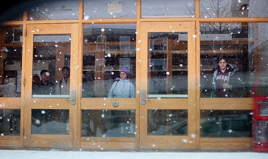 Students wait in the foyer for the shuttle as snow falls at Currier House. Rose Lincoln/Harvard Staff Photographer